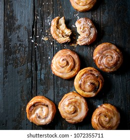 Homemade glazed puff pastry cinnamon rolls with custard and raisins over old dark blue wooden background. Top view, space. Rustic style. Square image