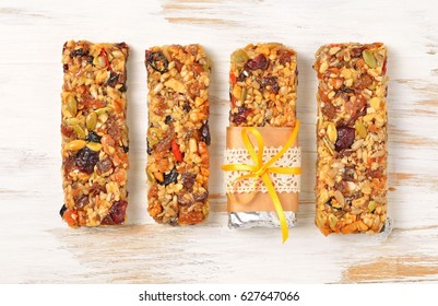 Homemade gluten free granola bars with mixed nuts, seeds, dried fruits on white wooden background. Top view.