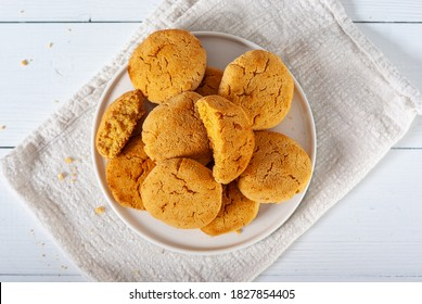 Homemade golden brown corn biscuits on a white plate and white wooden table, top view