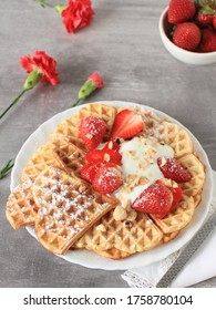 Homemade golden brown waffle topped with strawberries, nuts and whipped cream