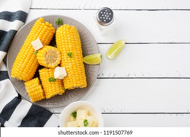 Homemade golden sweet corn cob with butter and salt on white table. top view.