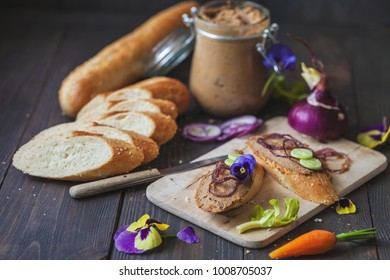 homemade goose paste on bread over a wooden table