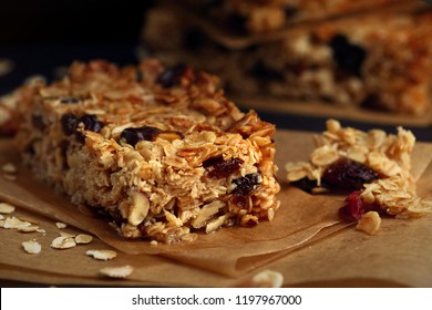 Homemade granola bars with nuts and cranberries over black background