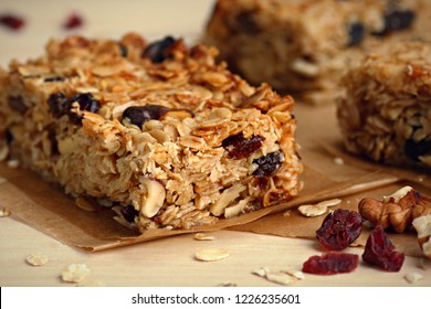 Homemade granola bars with nuts and cranberries over wooden background