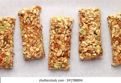 Homemade granola bars on white baking paper. Top view.