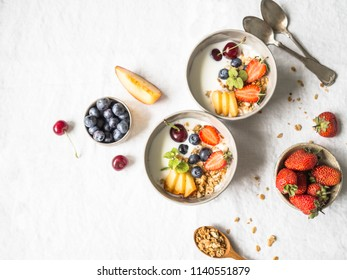 Homemade granola in a bowl with yogurt, peach, blueberries, cherries and strawberries on a table with a white tablecloth. Healthy breakfast on a white background. Top view. Copy space