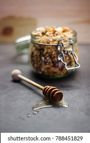 Homemade granola with cashew nuts, walnuts, coconut, dates, honey and oats in glass jar decorated by honey taker.