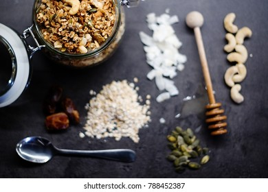 Homemade granola with cashew nuts, walnuts, coconut, dates, honey and oats in glass jar decorated by individual ingredients and honey taker, top view.