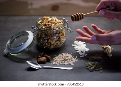 Homemade granola with cashew nuts, walnuts, coconut, dates, honey and oats in glass jar decorated by individual ingredients and honey taker.