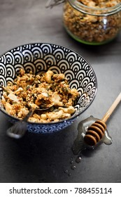 Homemade granola with cashew nuts, walnuts, coconut, dates, honey and oats in black and white pattern bowl decorated by honey taker and big glass jar on grey background.