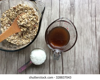 Homemade granola dry and wet ingredients with shredded coconut standing by