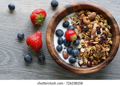 Homemade  granola with  fresh berry in wooden bowl