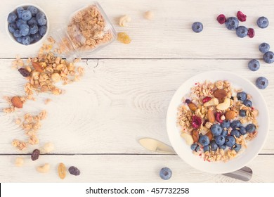 Homemade granola with fruit nuts and fresh yogurt on wooden board.