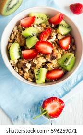 Homemade granola with fruits (strawberry and kiwi) in white bowl for healthy breakfast close up