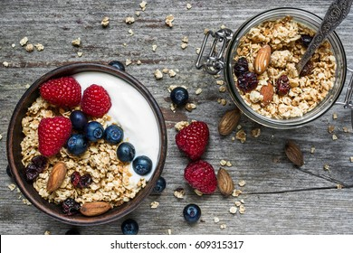 homemade granola with greek yogurt, nuts and fresh berries in a bowl with cereal in jar with a spoon over rustic wooden background. top view