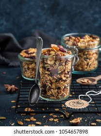 homemade granola (hazelnuts, raisin, dried cranberry, pumpkin, sesame and sunflower seeds) in glass jar. Selective focus. Blue background