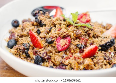 Homemade granola with honey, seeds, dried fruits, nuts and fresh berries served in a white bowl. Sweet breakfast