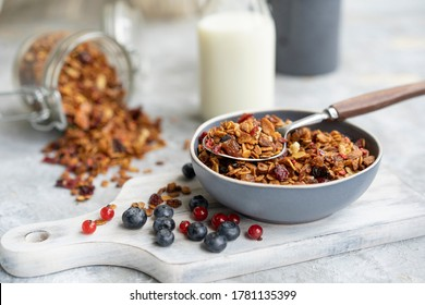 Homemade granola or muesli made of oats, nuts, honey, cinnamon, fruits in blue plate on white table with milk and flowers. Beautiful healthy snack on breakfast. Copy space, selective focus.
