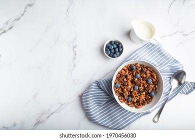 Homemade granola, muesli with pieces of dark chocolate, nuts and blueberries in bowl on white marble background. Healthy breakfast. Top view. Space for text.