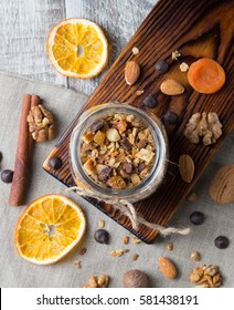 Homemade granola with nuts and dried oranges in jar with copy space, top view