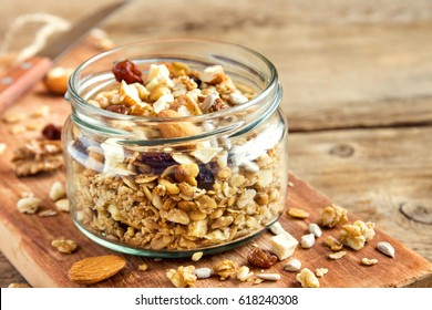 Homemade granola with nuts and seeds in glass jar for healthy breakfast - organic healthy vegan vegetarian diet detox recipe food granola musli.