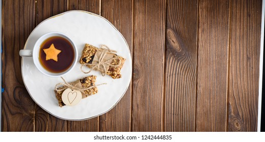 Homemade granola oatmeal energy bars, and cup of tea wyth orange star on white plate, healthy snack, copy space on wood desk