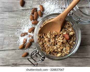 Homemade granola in open glass jar on with wooden spoon in the jar on wooden background