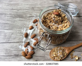 Homemade granola in open glass jar on with wooden spoon on a wooden background