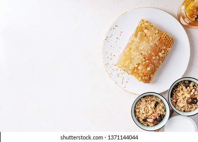 Homemade granola served with honey, honeycomb, milk, wooden spoons and honey dipper on white plate over white background. Top view
