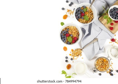 Homemade granola (with dried fruit and nuts) and healthy breakfast ingredients - honey, milk and berrieson white background