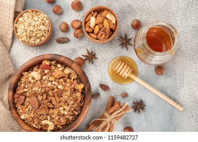 Homemade granola in wooden bowl with ingredients - oat, nuts, honey and spice cinnamon and anise.