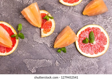 Homemade grapefruit popsicle with ripe grapefruit slices and fresh mint on dark concrete background. Healthy desserts. Lactose free ice cream