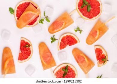 Homemade grapefruit popsicle with ripe grapefruit slices and fresh mint on light marble background. Healthy desserts. Lactose free ice cream.