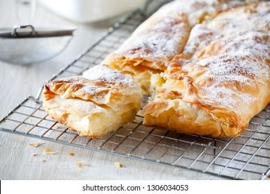Homemade greek custard pie with icing sugar and cinnamon