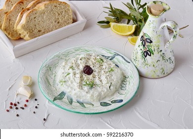 Homemade Greek traditional sauce tzatziki with cucumber, garlic, yogurt and lemon in a  bowl and  jar with olive oil on a  abstract background. Healthy eating concept. Mediterranean lifestyle.