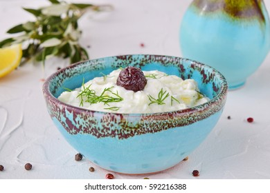 Homemade Greek traditional sauce tzatziki with cucumber, garlic, yogurt , olive oil and lemon in a traditional colored bowl on a white background. Healthy eating concept. Mediterranean lifestyle.