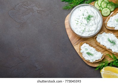 Homemade greek tzatziki sauce in a glass bowl with ingredients and sliced bread on a dark black stone background. Cucumber, lemon, dill, garlic. Top view, horizontal image, copy space