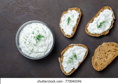 Homemade greek tzatziki sauce in a glass bowl with sliced bread on a dark black stone background. Top view, horizontal image, copy space