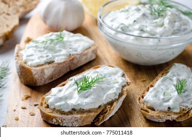 Homemade greek tzatziki sauce in a glass bowl with sliced bread on a wooden board. Close-up, horizontal image, selective focus on bread