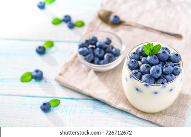 Homemade  greek yogurt, and fresh berries blueberries in a  jar with a spoon over rustic wooden background