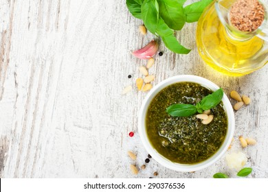 Homemade green basil pesto sauce and fresh ingredients. Italian Cuisine. Healthy food, diet and cooking concept. Food background with copy space. Top view.