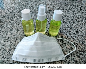 Homemade green hand sanitizer with a medical mask on a granite table