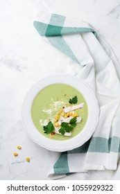 Homemade green soup puree from broccoli, avocado, chicken and corn with cream in rustic ceramic plate on white concrete background. Selective focus. Top view.