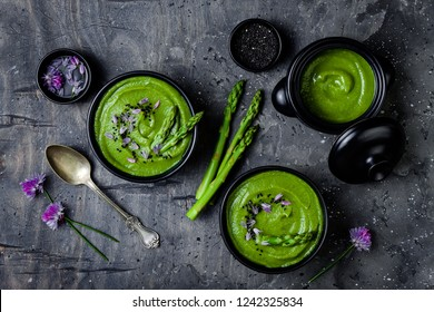 Homemade green spring asparagus cream soup decorated with black sesame seeds and edible chives flowers