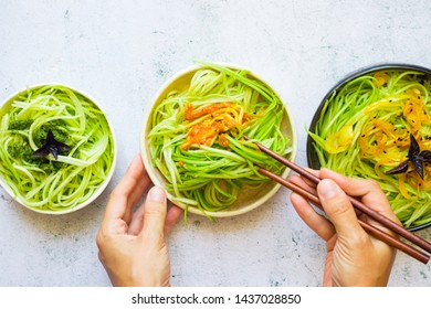 Homemade green zucchini spaghetti or pasta in bowl with chopsticks. Woman hands holds vegan, vegetarian healthy food. White background table.