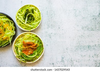 Homemade green zucchini spaghetti or pasta with sauce in bowl with chopsticks. Vegan, vegetarian healthy food. White background table. Space for text.