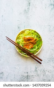 Homemade green zucchini spaghetti or pasta with sauce in bowl with chopsticks. Vegan, vegetarian healthy food. White background table.