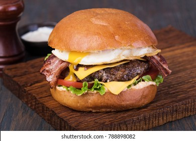homemade grilled burger on wooden board