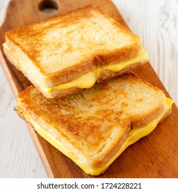 Homemade Grilled Cheese Sandwich on a rustic wooden board on a white wooden table, low angle view. Copy space.