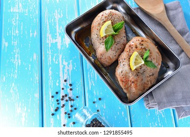 Homemade grilled chicken on the black metal tray.Decorated with ingredients and lemon sliced on blue pastel wooden table. Concept about food preparation in the kitchen. Home Cooking. Healthy Foods.